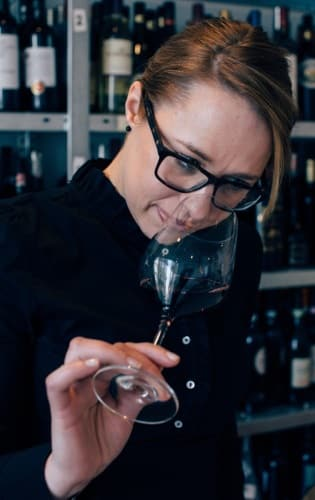 Linda Sorby doftar på ett rödvin i ett glas