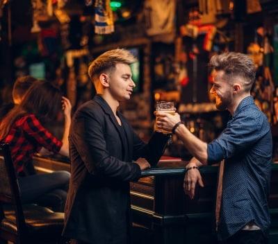 2 glada killar i en pub som dricker öl