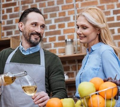 ett par som tar ett glas vin i köket