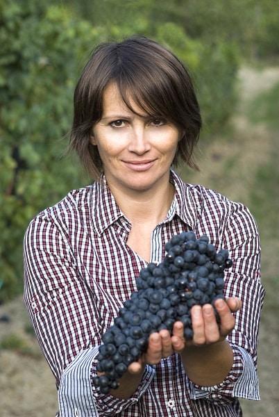 kvinna som håller upp en klase med druvor