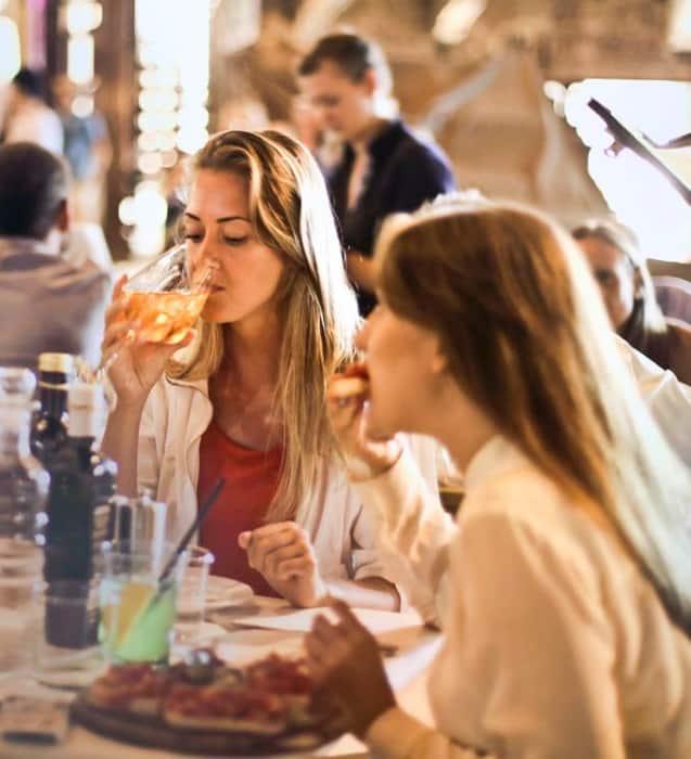 två unga tjejer som sitter och äter middag
