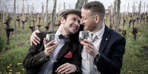 2 killar som kramas och skålar i vin