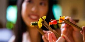 asiatisk flicka äter med innar