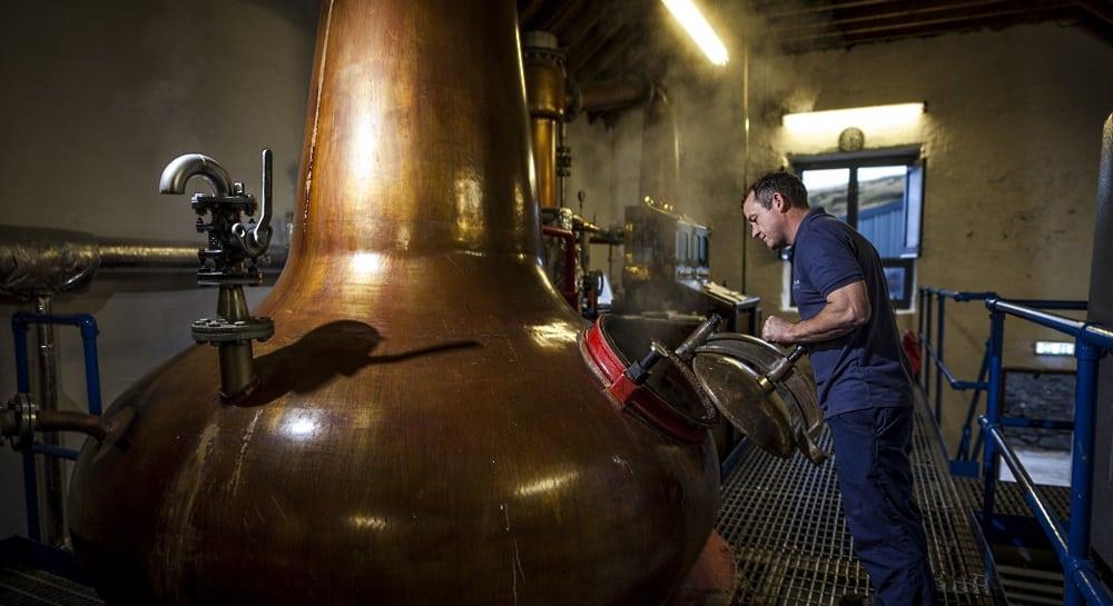 man framför whiskypannor i koppar destilleriet Kilchoman