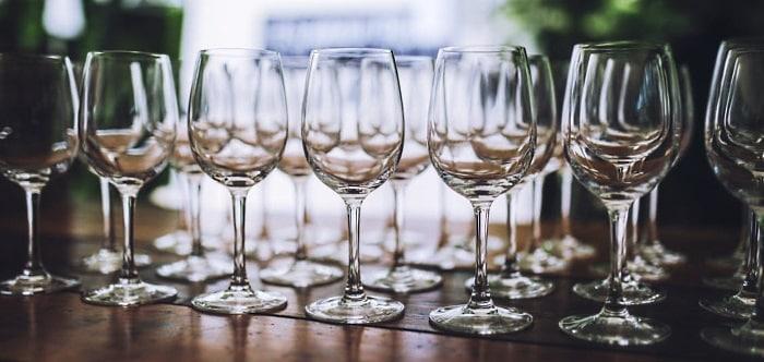 ett tiotal tomma vinglas som står på rad och väntar på vinprovning