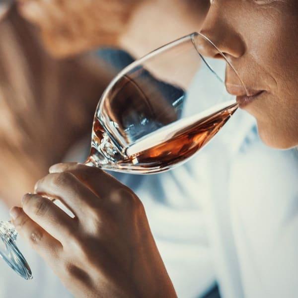 på vinprovning och en hand som håller ett vinglas framför munnen