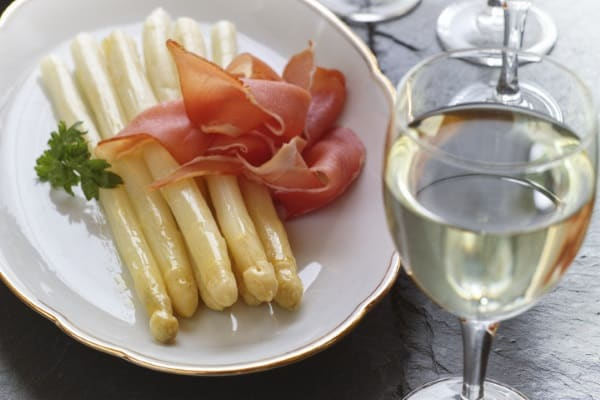 vit sparris med lufttorkad skinka och ett glas vin