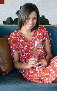 kvinna med vinglas i handen sitter på en soffa i en röd klänning