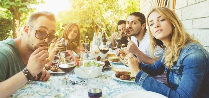 sommarviner en grupp männniskor vid ett bord ute och äter