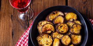Medelhavet: krispiga aubergineskivor på tallrik och ett glas rött vin