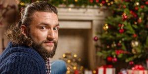 julklappar - snygg kille framför granen