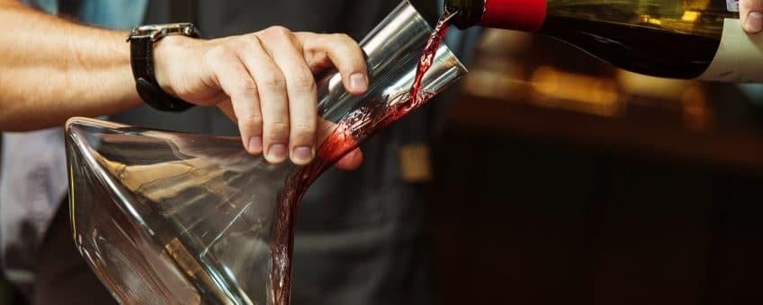 Dekantera - en man som dekanterar rött vin