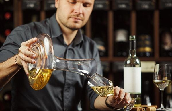 Dekantera - man man som dekanerar vitt vin ur karaff
