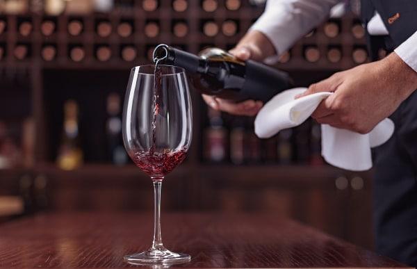 dekantera - en man som häller vin i ett glas