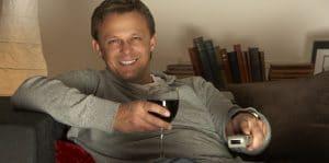 vinfilmer - kille ser på tv med vinglas