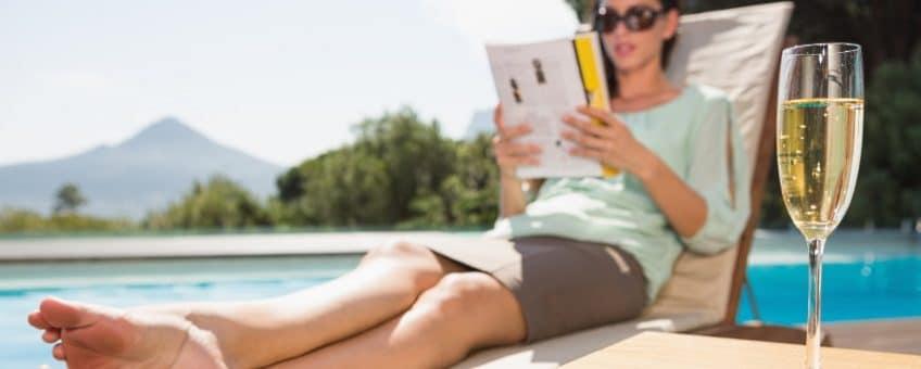 sommarböcker - tjej läser bok med ett glas champagne på bordet
