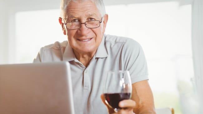 vinprovning - en öldre man med vinglas framför datorn