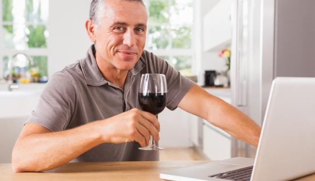 vinprovning - en man skålar med ett glas framför datorn