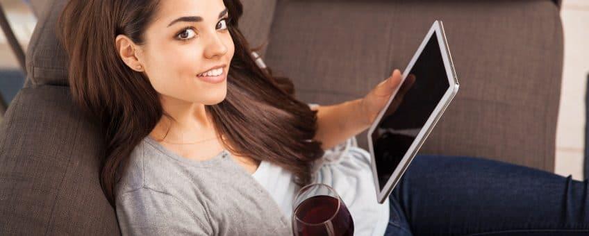 vinprovning - en kvinna med vinglas framför surfplatta