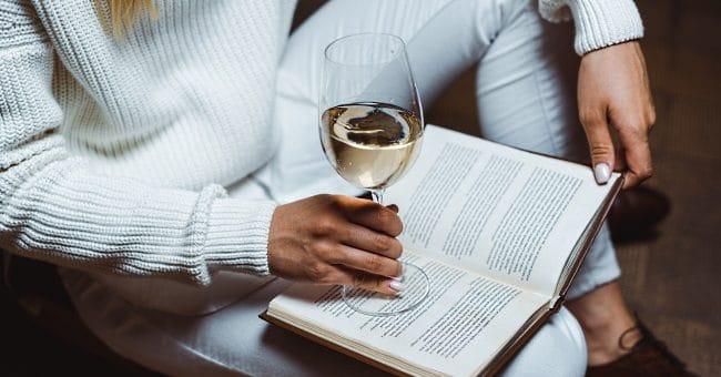 böcker om vin - en kvinna som läser med ett glas vin