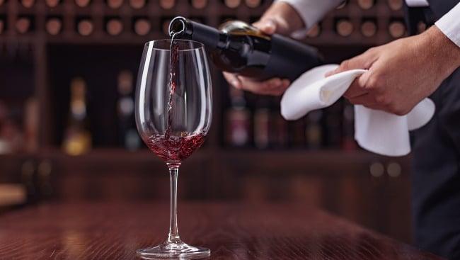 bordeaux-druvor-kypare-som-häller-upp-vin-i-glas