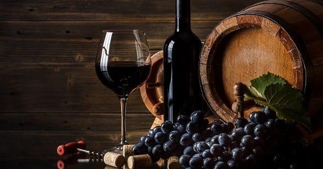 vinflaska, fat och röda druor