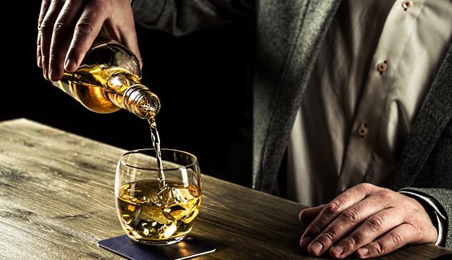 Japansk whisky - en man som häller upp whisky ur en flaska