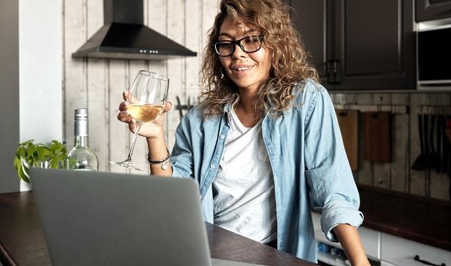online-vinprovning-samma-tjej-i-köket-framför-datorn-med-ett-glas-vin