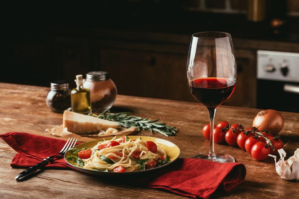 glas rött vin tallrik pasta tomat rustikt rosmarin
