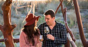 ett par som sitter ute och dricker vin