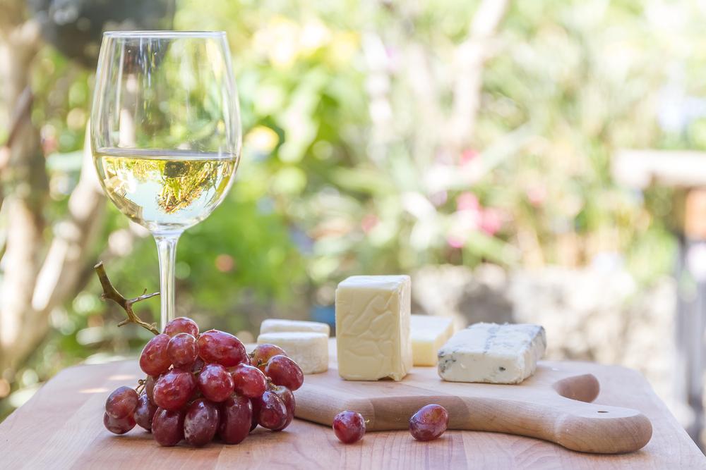 Osttallrik med vitt vin och röda druvor