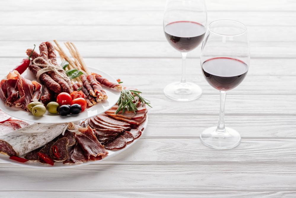 glas rött vin med chark sparris oliver